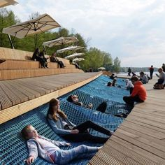 Paprocany Lake Shore Redevelopment: Location: Tychy, Poland Year of Construction: 2014 Architects: RS+ The waterfront site is a part of a large recreational redevelopment of a lake shore area in Poland. Wood decked walkways guide people through the space while offering sunken seating made of comfortable hammock like netting. Walkways are also illuminated with efficient LED lighting.