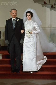 DECEMBER 9, 1967: President Lyndon Johnson escorts his elder daughter, Lynda Bird Johnson, downstairs at the White House.  She married Charles S. Robb, USMC, that afternoon.  American fashion icon Geoffrey Been designed the bridal gown.