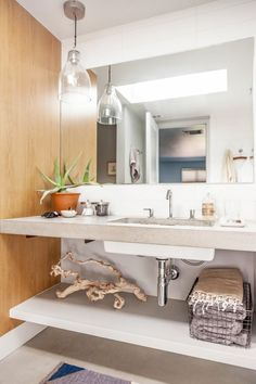 Texture-filled bathroom with concrete countertops, a glass pendant light, and a wire basket doubling as bathroom towel storage