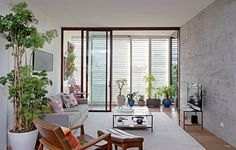 Com muitas plantas, a sala do seu apartamento vai parecer um verdadeiro quintal. O verde pode estar em vasos apoiados no chão ou pendurados na parede, como no projeto do escritório Apiacás Arquitetos