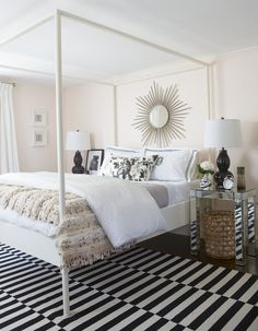 pink walls framing a silver sunburst mirror over an Ikea Edland Four Poster Bed dressed in black and white monogrammed bedding, gray quilt, black and white polka dot duvet as well as a Moroccan wedding blanket flanked by mirrored bedside tables topped with Robert Abbey Double Gourd Lamps in Black alongside a black and white striped rug layered over wood floors.