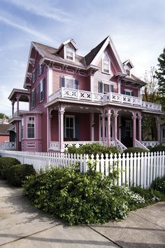 Pink Victorian home in downtown Savannah, Georgia. Love the white picket fence going around it & the upper porch above the porch.