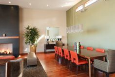 The dining area features a high ceiling, hardwood floor and striking pimento accents.