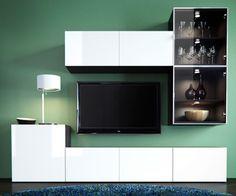 BESTÅ-tv- ja -säilytyskaluste, jossa on valkoiset ja vitriiniovet. Huoneessa valkoinen pöytävalaisin, sininen pyöreä matto ja vihreä seinä.