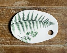 A freeform, stoneware, cheese plate. Imprinted with leaves gathered along the bridleway in East Woodlands, where the ferns grow as tall as me.Approx 26cm length.For international shippi...