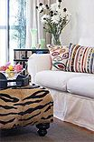 Living room with scrap fabric throw pillows, white casual sofa, tiger ottoman and mirrored cabinet