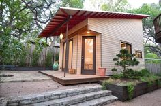 Exterior of small photography work studio in Austin at twilight with wood siding and stone steps