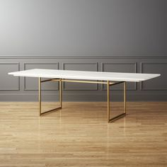 Shop Carmen Mango Wood Dining Table.   White-painted mango wood stretches long and lean atop minimalist brass legs.  Table's surface is wire brushed by hand for unique worn effect.