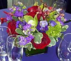 This is a cube vase floral arrangement that features roses, stock, cymbidium orchids and hydrangea in a red, purple and green color scheme. See our entire selection at www.starflor.com.  To purchase any of our floral selections, as gifts or décor, please call us at 800.520.8999 or visit our e-commerce portal at www.Starbrightnyc.com. This composition of flowers is generally available for same day delivery in New York City (NYC).  SQ319