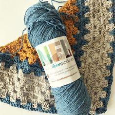 A Sunny Day Shawl Kit - a triangle shawl crochet pattern and 3 skeins of yarn to create the shawl pattern.