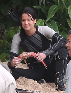 Jennifer Lawrence looking sad while eating a fish on the set of The Hunger Games: Catching Fire
