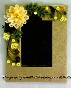 Photo frame decorated with quilled flowers n leaves made out of paper strips.