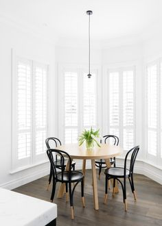 Dining nook in bay windows: white plantation shutters, round wooden dining table, black dipped Thonet bentwood chairs, timber floorboards, glass pendant light with black cord