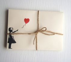 banksy style envelopes 5 ivory pastel colored, with red and black Banksy loveheart balloon girl on the front. Banksy style. cream stationary. £3.50, via Etsy.