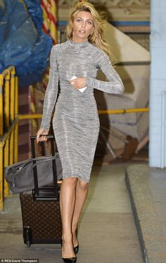Abbey Clancy.. Grey polo neck bodycon dress.. black pointed heels.. grey Hermes Birkin.. Louis Vuitton suitcase..