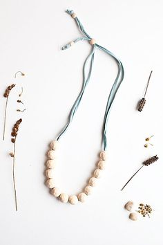 Modern Moms...Busy Babes! Welcome to Bumble and Bee Studio!  GRAND OPENING OFFER! TAKE 20% OFF YOUR ORDER WITH CODE: WELCOME20  Introducing the LILY necklace......  This extra long adjustable necklace features 14 unpolished 25cm wooden beads each sanded flat in numerous sections on the surface of each bead. Made for extra play and longer interaction this necklace works unbelievably well for teething babies and is our number 1 recommended product for teething! Soft to touch like sanded silk…