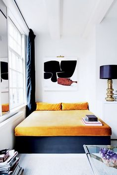 Luxe bedroom with large art, a gold lamp, and a small bed