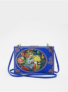 """A clutch that our favorite bookworm, Belle, would <i>love</i>. The gorgeous cobalt blue faux leather clutch is fashioned into the shape of a hard-back, with a gold tone metal closure. The stained glass graphic of <i style="""""""">Beauty and the Beast</i> proves that beauty can exist on the outside; the multiple interior zip pockets prove it exists on the inside as well.<div><ul><li style=""""list-style-position: inside !important; list-style-type: disc !important"""">58"""" removable strap</li><li…"""