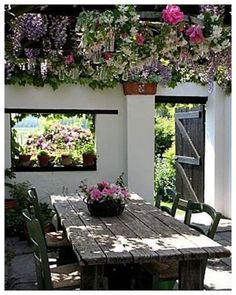 wisteria covered pergola,reclaimed wood table and the window carved into the wall.