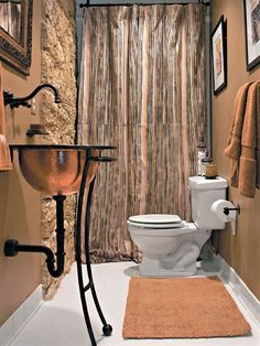 A new hammered-copper sink and canvas shower curtain transform this bath. The sink, a vessel-style bowl, sits in an iron base and is paired with an aged bronze faucet.