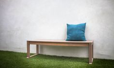 White Stucco wall, wood bench, Synthetic turf, and a blue outdoor pillow. http://www.trulandscape.com/modern-backyard-remodel/