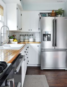 Feel like a chef in this simple, classic white kitchen featuring stainless steel appliances and butcher block countertops. This space is the perfect place to prepare family meals!