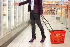 Low section of woman in front of refrigerator carrying basket in the supermarket Stock Photo
