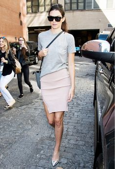 Kendall Jenner wears a gray t-shirt, blush pink pencil skirt, metallic pointed-toe pumps, a crossbody bag, and rectangular sunglasses