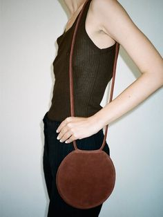 Circular folding bag with a rolled shoulder strap for tying in a bow or knot, 2 interior slit pockets, magnet closure Can be worn over the shoulder, around the waist or on the arm A bag just for your essentials Limited quantity available 7 x 7 1/2
