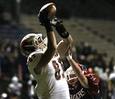 Justin Musser pulls in a first-quarter touchdown for Eastside Catholic in front of Nathan Hale's Evile Kalaniuvalu. See more of Seattle Times photographer Mark Harrison's photos from the game.