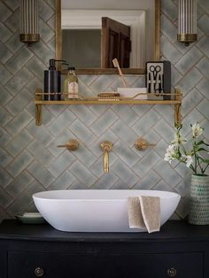 Brass fixtures play off the golden-colored grout between these herringbone-placed subway tiles for a rich look.