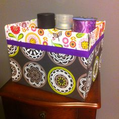 Covered a cardboard box with scrapbook paper and ribbon. Now a cute storage box :)