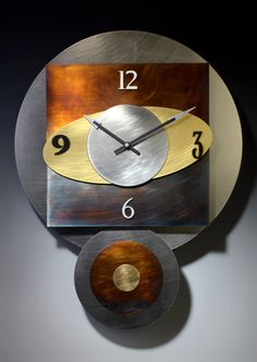 Orbit Pendulum Clock by Leonie Lacouette. This big, geometric pendulum clock is a three-dimensional construction of layered metals: brushed stainless steel, brass, aluminum and hand-patinated nickel silver in rich browns, blues and golds. Signed on back. Uses 2 AA batteries (included). All metal coloring is done by hand and will vary from piece to piece.