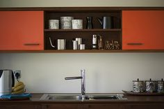 homes - edinburgh house: kitchen area with orange cupboards and stainless steel sink