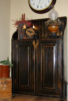 Beautiful-Distressed black with rubbed stain – one of my favorite combinations: paint black, distressed with sanding, and then the bare wood is stained for aging. For example, Walnut stain makes a beautiful contrast to black. distressed finish.Note how she sanded the area where the cabinet knobs go to simulate natural wearing. Wanna do this with our spare bedroom furniture