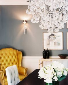 Chandelier Photo - A yellow wingback chair in a dining room with gray walls