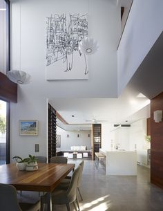 Modern Living Spaces // natural light in this double height space pairs well with the polished concrete floors, wood table and crisp white walls at the Sunshine Beach House By Shaun Lockyer Architects