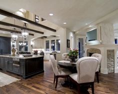 How awesome is that corner fireplace! Love the open ceiling as well. This kitchen works. Kitchen by Schrader & Companies Via Houzz