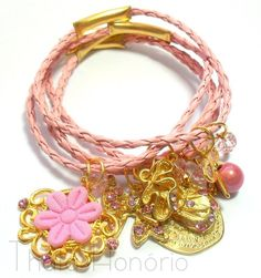 Cód: PUL422 <br>Conjunto com 5 pulseiras de couro, pingentes em banho de ouro, flor de guipir, pedra de resina e strass.
