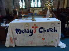 L19 Messy Church altar cloth - felt tipped pens on sheet; happy faces as Jesus smiles when we come to his table.