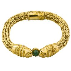 Van Cleef & Arpels Etruscan Revival gold lion bracelet. 18K gold mesh bracelet by Van Cleef & Arpels. The bracelet is fashioned after the Etruscan revival style. It features a mesh chain linked body, with two lion heads coming together on a cabochon emerald of approx. 2.0cts.