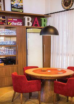 Um espaço de lazer foi criado, com mesa de jogos e área de bar. As cadeiras, revestidas em suede vermelho, contrastam com a madeira predomin...