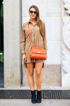 Foto de look total camurça com vestido nude e botas pretas, arrematado por bolsa dolce gabanna laranja