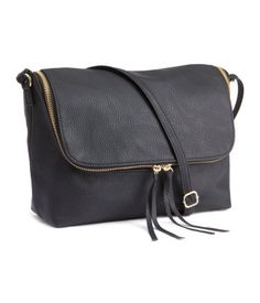 Shoulder bag in imitation leather. Zip around cover flap. Narrow, adjustable shoulder strap, and one inner compartment with zip. Lined. Size 7 x 11 in.