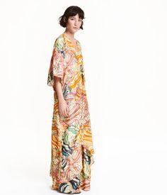 Wadenlanges Oversize-Kleid aus Viskosestoff. Modell mit V-Ausschnitt und Knöpfung vorn. Überschnittene Schultern und Kurzarm. Seitentaschen und etwas verlängertes Rückenteil.