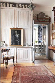 Saxå herrgård. Konstverk. Från kapprummet på nedervåningen ser man in i frukostrummet. Stolen är broderad i petit point, från 1880-talet och inköpt från Oscar Bernadottes hem på Frötuna gård. Oscar den II i grisaille-måleri, porträtterad av Oscar Björck, överblickar rummet från sin guldram.