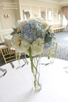 peach, blue and white centerpiece: white hydrangeas, blue hydrangeas, peach spray roses, dusty miller, hanging amaranthus with curly willows in side the cylinder vase \\ wedding centerpiece