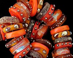 A beautiful OrGaNiC set of 36 glass discs made in various shades of orange and warm tones. Accents include pure silver wire and silver glass.