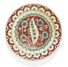 AN IZNIK POLYCHROME POTTERY DISH WITH A RED GROUND, TURKEY, CIRCA 1570-75 decorated in underglaze cobalt blue, emerald green, and relief red with dark green outlines, featuring a saz leaf containing a stem of marguerites, in between sprays of rosettes, the border with a stylised foliate design, foliate details on exterior, old collection label to underside 31.5cm. diam. Sotheby's