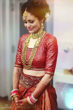 Indian Wedding Jewelry - Gold Choker with Gold Long Necklace | WedMeGood | Bride in a Red Lehenga with Gold Jewelry and Flower in Hair #wedmegood #indianbride #indianwedding #red #bridal #lehenga #gold #jewelry #choker #maangtikka